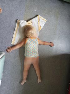 Ein Kleinkind liegt mit nackigem verpixeltem Po platt auf dem Boden