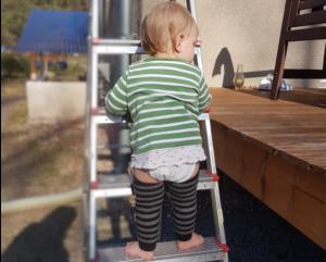 Ein 1 jähriges Kind von hinten, steht auf einer Leiter und trägt Stulpen sowie ein Gästehandtuch als Backup