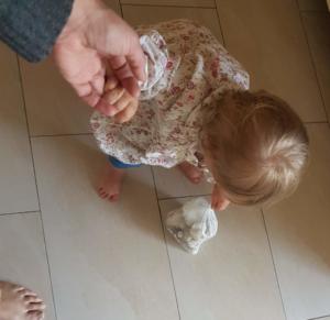 Kleinkind ist an der Hand von Mama undträgt einen Müllbeutel