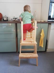ein kleinkind steht auf einem Learning Tower. Rückenansicht. Trägt Wollwindelüberhose und Stulpen