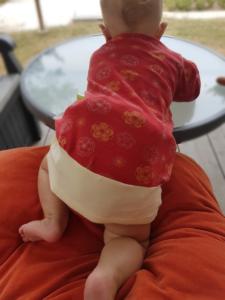 Baby mit langem Shirt zu sehen von hinten