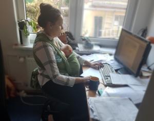 Norma Burow sitzt am PC mit Neugeborenem im Tragetuch an einem Arbeitstisch mit Blick aus dem Fenster