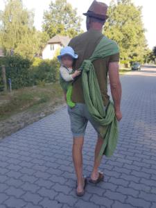 Mann mit Tragetuch in Hüftbindeweise trägt Baby
