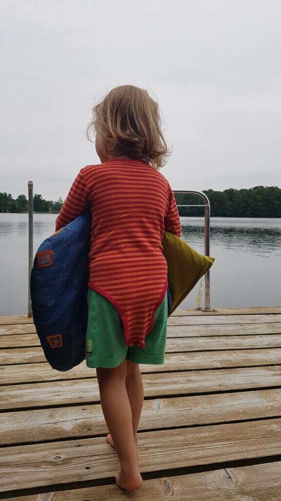 Kind von hinten trägt Kissen auf eine Terrasse am See.
