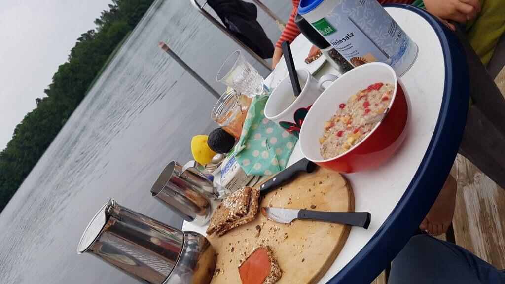 Frühstückstisch mit Espressokanne, Brot und Müsli.