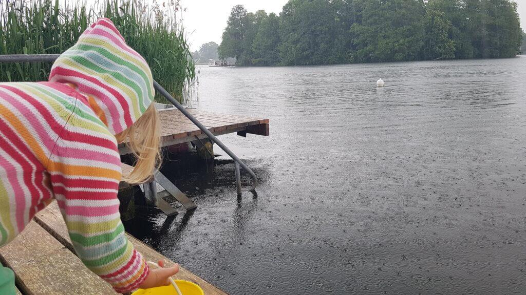 Regentropfen fallen auf den See. Ein Kind mit Kapuze bückt sich runter zum Wasser.