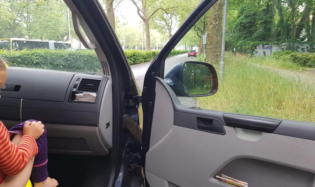 Blick durch Front- und offene Beifahrertürscheibe eines Autos mit Kind auf dem Beifahrersitz und Töpfchen