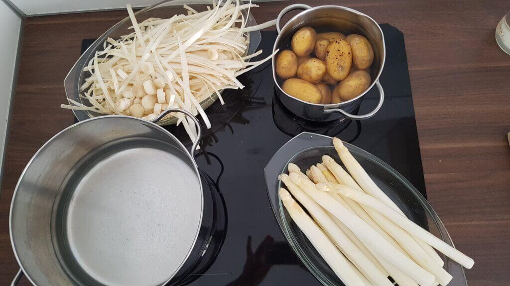 Auf dem Herd: Töpfe mit Kartoffeln, Spargel und Spargelschalen