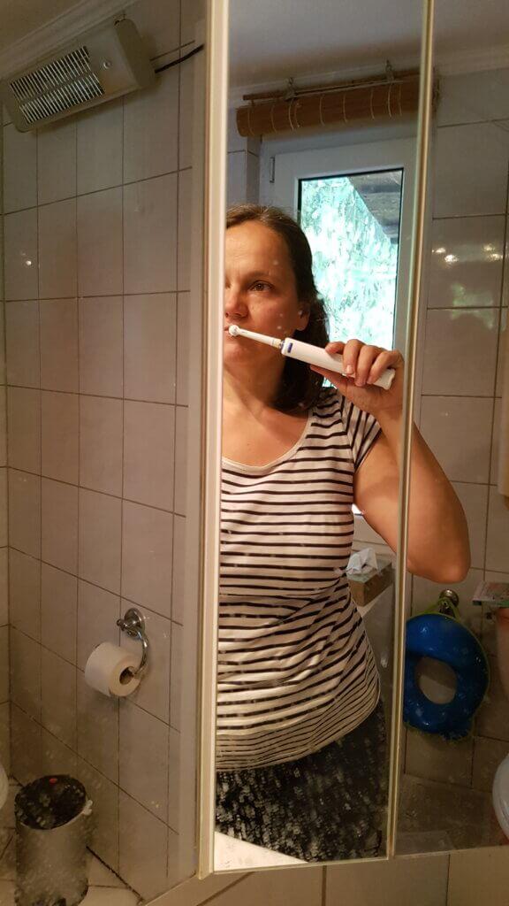 Blick in Spiegel, Norma Burow beim Zähneputzen, im Hintergrund, WC, WC-Papier und Toilettensitz fürs Kind.
