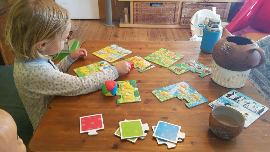 Kind schon bettfertig spielt noch Puzzle am Tisch mit Puppe, Teebecher, Teekanne.
