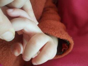 Baby und Mama Finger ineinander verhakelt