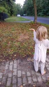 Meine Tochter, noch immer im Schlafanzug, winkt Papas wegfahrendem Auto hinterher zum Abschied.