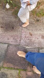 Beine von Kind und Erwachsenem ohne Schuhe. Barfuß über Gras, Sand und Gehwegplatten.