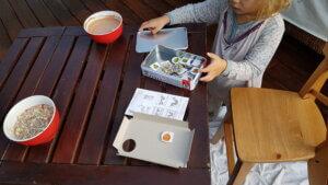 Rote Schüsseln mit Müsli und Schoko-Joghurt auf Holztisch mit einem Raupe Nimmersatt Spiel als Begleitung.