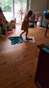 Kind steigt auf Schrubberbürste und Scheuerlappen, die auf Holzfußboden bereit liegen zum Saubermachen.