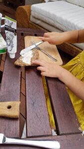 Kinderhände verteilen mit eigenem Messer Fischcreme aufs Brot.