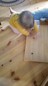 Blick auf Fußboden mit kleinem Kind, das auf einem Tablett mit Murmeln spielt.