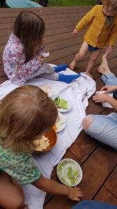 Sitzende Kinder auf Holzterrasse und Picknickdecke essen gemeinsam Guacamole, Hummus und Gemüsesticks.