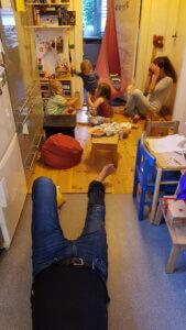 Blick in abendlich turbulente Spielecke mit 3 Kindern, einer Frau und den Jeansbeinen eines Mannes.