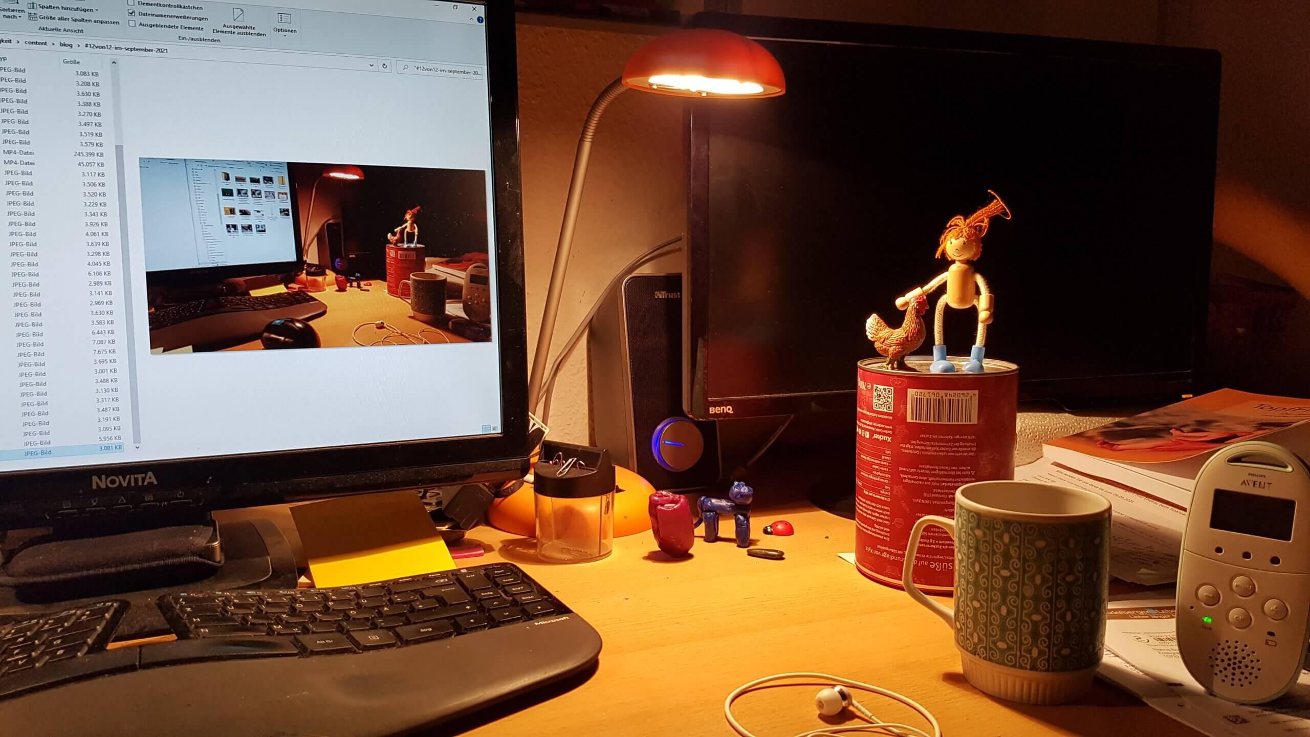 Blick auf Computer Monitor mit Schreibtischlampe, Biegepuppe, Teetasse und Babyphone.