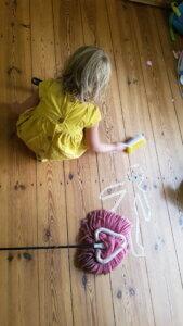 Kind mit Handfeger und Staupmop auf Holzfußboden hilft beim Saubermachen.